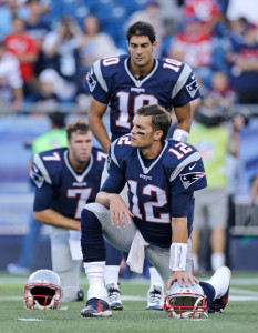"AUG. 13: New England Patriots quarterback Tom Brady stretches before the team's first preseason game during a warmup with teammates  Jimmy Garoppolo (10) and Ryan Lindley (7) in Foxborough, Mass. A day earlier, Brady sat in a Manhattan courtroom as his lawyers met with U.S. District Judge Richard Berman and NFL Commissioner Roger Goodell's legal team in an effort to resolve the so-called ""Deflategate"" controversy."