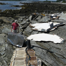 The remains of a motor boat that litter the rocky shore of Peaks Island are expected to be cleaned up this weekend.