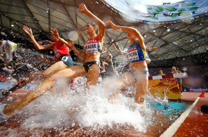 AUG. 24: Athletes jump a water obstacle in the women's 3,000-meter steeplechase final during the  IAAF World Championships at the National Stadium in Beijing.