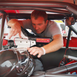 After qualifying for the poll position, Eddie MacDonald puts his helmut into his car before the start of the Oxford 250. Carl D. Walsh/Staff Photographer