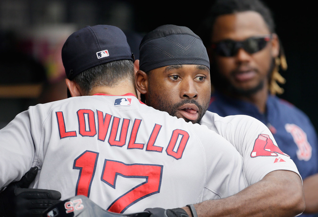 Boston Red Sox's Jackie Bradley Jr. hugs bench coach Torey Lovullo after scoring from third on a single by teammate Brock Holt during the eighth inning against Detroit. Bradley previously arrived at third on a three-run triple to right field. The Associated Press