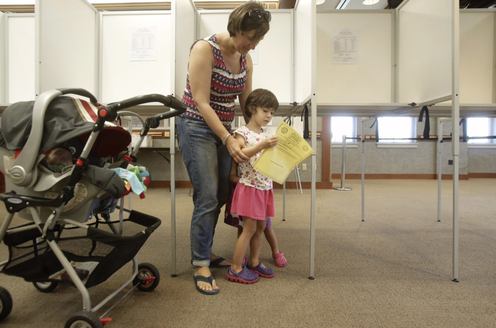 Isabel Alves, 4, looks at the ballot for the Scarborough school budget vote while her mother, Laurie Alves, votes at the Scarborough Municipal Complex on Tuesday. It was the third time Alves has voted for the school budget, which she says she would like to see approved so no school programs get cut.
