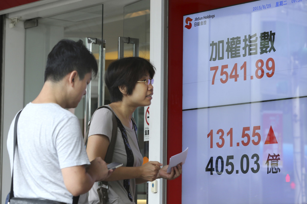 Pedestrians watch monitors displaying the benchmark of the Taiwan Stock Exchange in Taipei on Tuesday. Chinese stocks plunged again Tuesday morning, a day after the country's main benchmark suffered its biggest tumble in eight years. The Associated Press