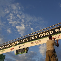Howard Kramer of Dave McGillivray Sports Enterprise makes a last-minute tweak to the banner at the finish line of the TD Beach to Beacon 10K.