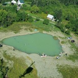 Aerial view of pond where plane wreckage was discovered Thursday morning. Crews are draining the pond so emergency responders can recover the pilot's body and the plane. Maine Forest Service photo