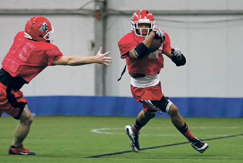 Brandon Bennett, right, looks for some room to run on a kick-return drill as Kevin Corbin pursues during a practice for the Southern Maine Raging Bulls. Jill Brady/Staff Photographer