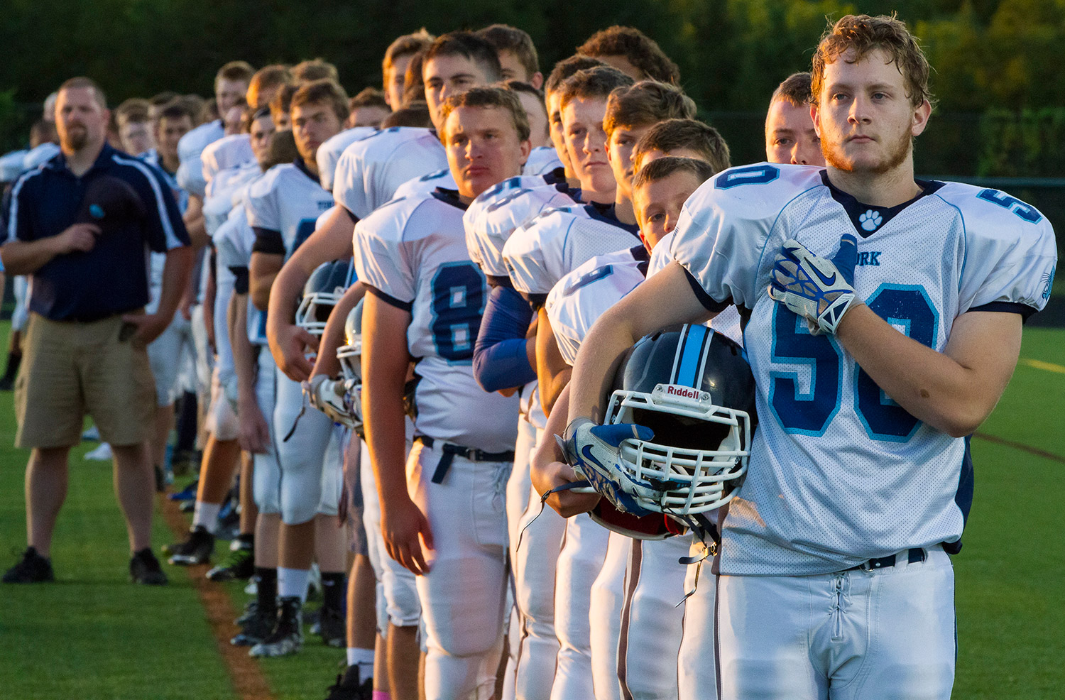 The York High School Wildcats stand for the Pledge of Allegiance at the start of their season opener Friday night at Falmouth.