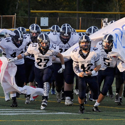 The Portland Bulldogs blast through their banner to begin the football season Friday night against the Scarborough Red Storm.