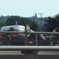 A rescue crew works on Interstate 295 in Portland after a car flipped onto its roof Thursday afternoon.