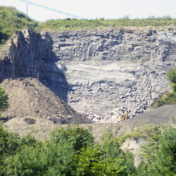 A city lawsuit alleges that a May blast at the West River Road pit and quarry owned by Steve McGee Construction violated city standards.