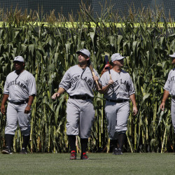"Portland Sea Dogs Forrestt Allday, second from left, joins teammates walking onto the field from a wall of corn stalks as part of the ""Field of Dreams"" game at Hadlock Field Sunday. Joel Page/Staff Photographer"