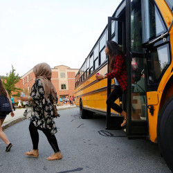Students arrive on a bus for the 7:50 a.m. start of their school day in Westbrook.