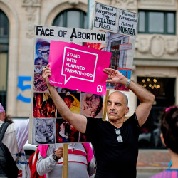 Ron Botting, 59, of Portland, tries to cover up anti-abortion signs held by David (who declined to give his last name) during a Planned Parenthood rally in Monument Square.