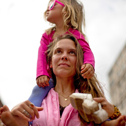 Taylor Gendron of Athens and her daughter, Eliote-Odette Lavenu, 3, stand and watch the rally for Planned Parenthood in Monument Square.