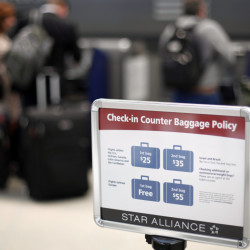 A sign describes an airline's baggage fees at Philadelphia International Airport. But the cost of flight cancellation or change fees are sometimes hidden in a ticket's fine print.