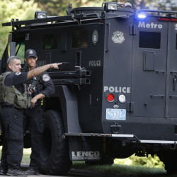 Law enforcement officials talk beside an armored vehicle Wednesday after multiple shots were fired into a Millis police cruiser in Millis, Mass. Police say the cruiser then crashed into a tree and caught on fire. No injuries were reported. The investigation is continuing.