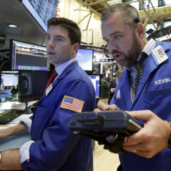Specialist Thomas McArdle, left, and trader Kevin Lodewick work on the floor of the New York Stock Exchange on Wednesday. On Thursday, stocks continued to gain.