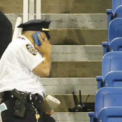 A police officer stands next to a drone that crashed at the U.S. Open Tennis Championships late Thursday.