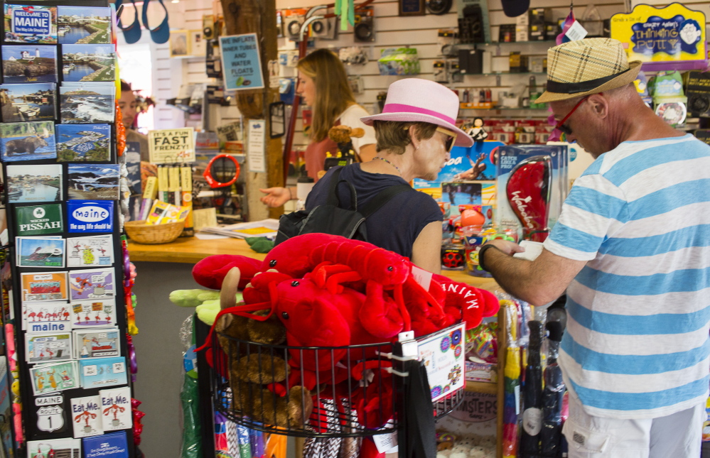 """Visitors browse in the Ogunquit Camera Shop, which also sells toys and kites. Tracy Smith, who has worked there for 21 years, said business has been excellent this summer, partly because """"people are feeling better about the economy, better about their spending."""""""