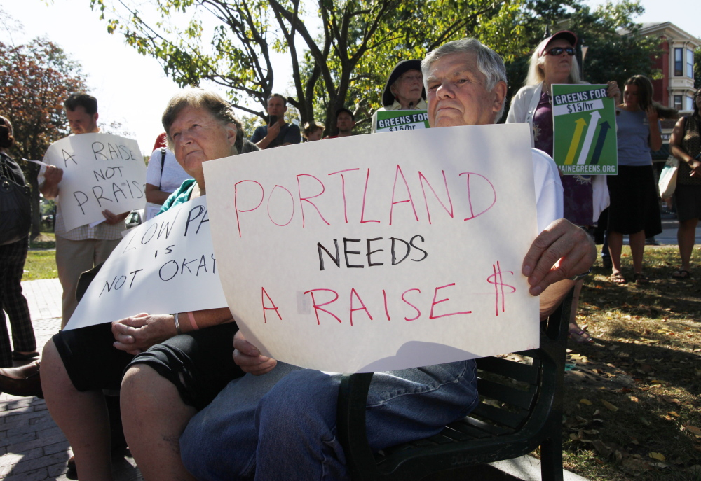 Elden McKeen, right, and his wife, Pat, left, listen to speakers at the Labor Day rally in Portland.