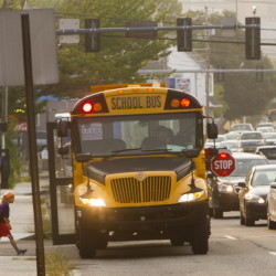 Children board their school bus Thursday, under the supervision of parents, at the stop at Frances and Congress streets in Portland. A change in school start times led to the relocation of some bus stops to main streets with heavy morning commuter traffic.