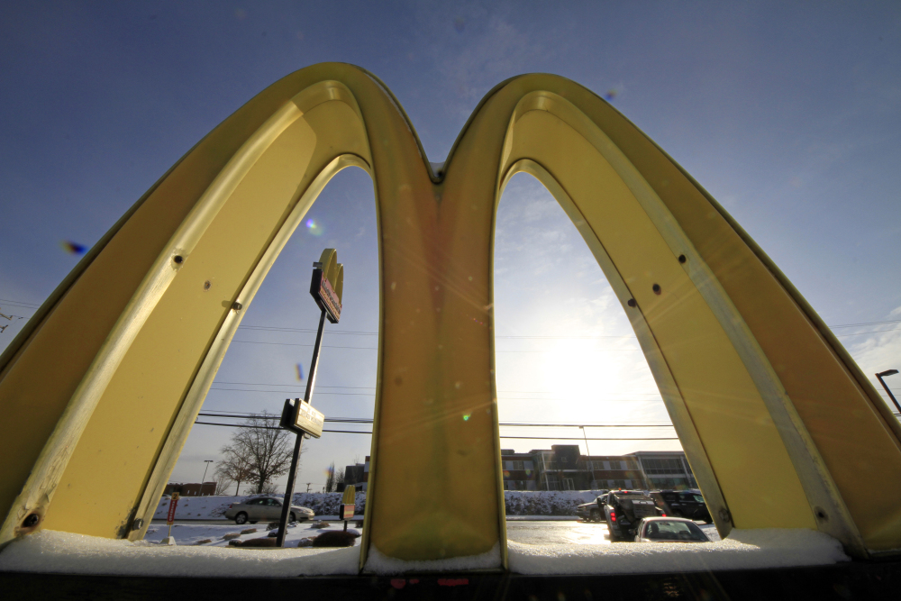 This Jan. 21, 2014 file photo, cars drive past the McDonald's Golden Arches logo at a McDonald's restaurant in Robinson Township, Pa.