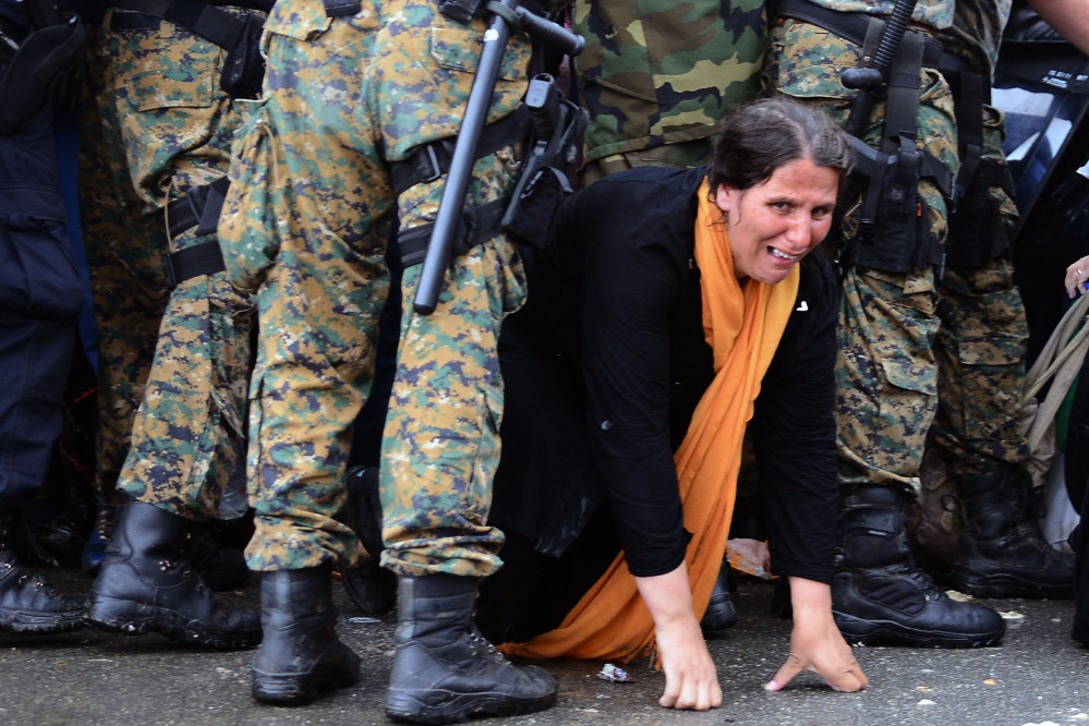 A woman crawls through a police blockade in Gevgelija on Thursday, as 7,000 trekking migrants cross into Macedonia from Greece. The Associated Press