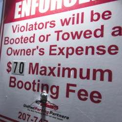 A sign at a Unified Parking Partners lot on Shepley Street warns of the consequences of violations. The company has been under fire for its car-booting practices, but officials say their policy is fair and clearly spelled out.