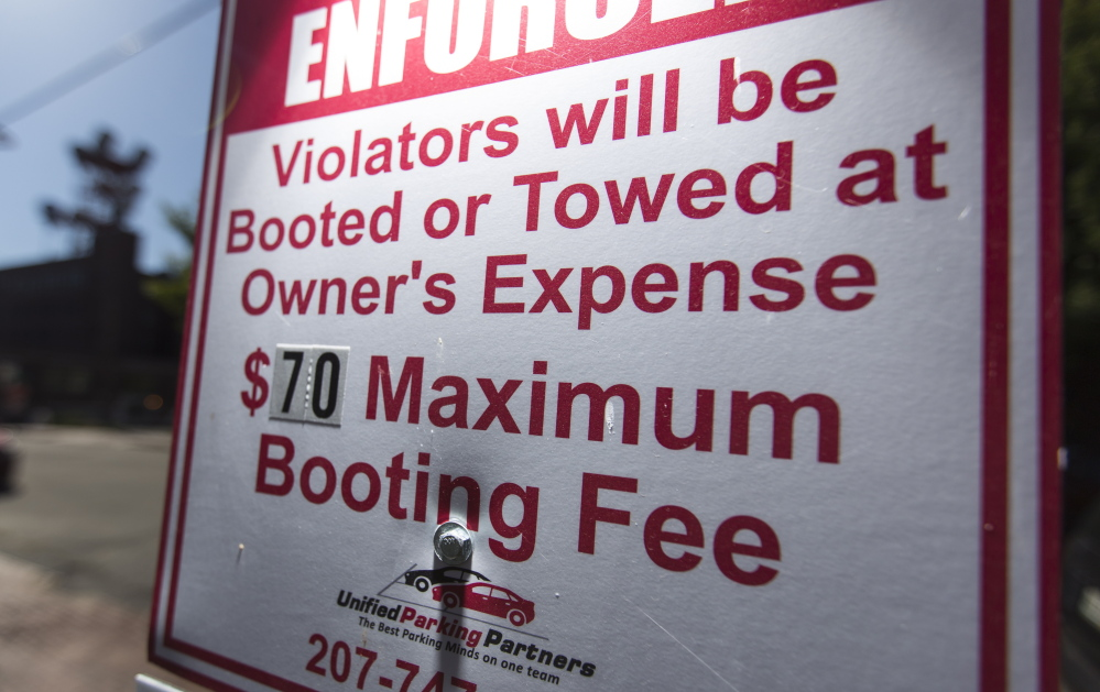A sign at a Unified Parking Partners lot on Shepley Street warns of the consequences of violations. The company has been under fire for its booting practices, but now says it will relax its practice of booting vehicles with expired parking tickets.