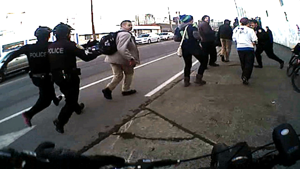 In this image from a Seattle police body camera video, officers move in to make an arrest during a Black Lives Matter demonstration in January.  The Associated Press