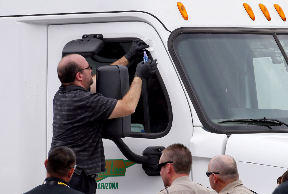 Arizona Department of Safety officers inspect a tractor-trailer with a bullet hole in the passenger door shortly after it was shot on Thursday in Phoenix.