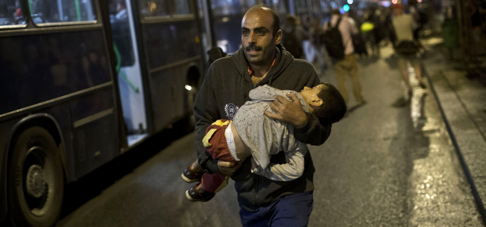 A man carries a child as he runs to board a bus provided for refugees in Hungary after Austria said that it and Germany would let them in.
