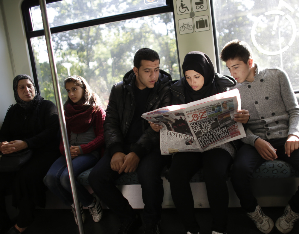 Syrians Reem Habashieh, flanked by her brothers Yaman, right, and Mohammed, ride a train in Berlin while reading a newspaper with special pages in Arabic for refugees. At left is the siblings' mother, Khawla Kareem, with 11-year-old daughter Raghad.