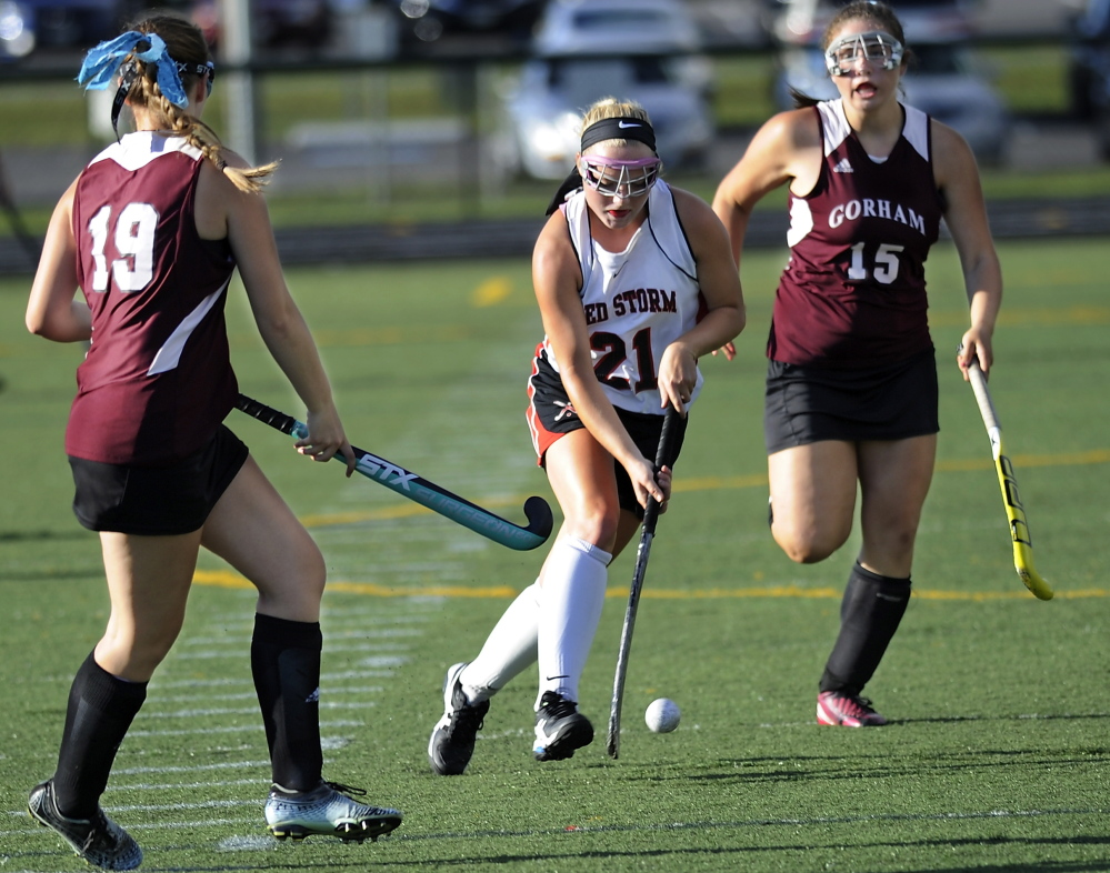 Ashley Levesque of Scarborough looks for room Friday while controlling the ball between Heather Woodbury, left, and Emmy Viernes of Gorham during Scarborough's 3-1 victory in field hockey.