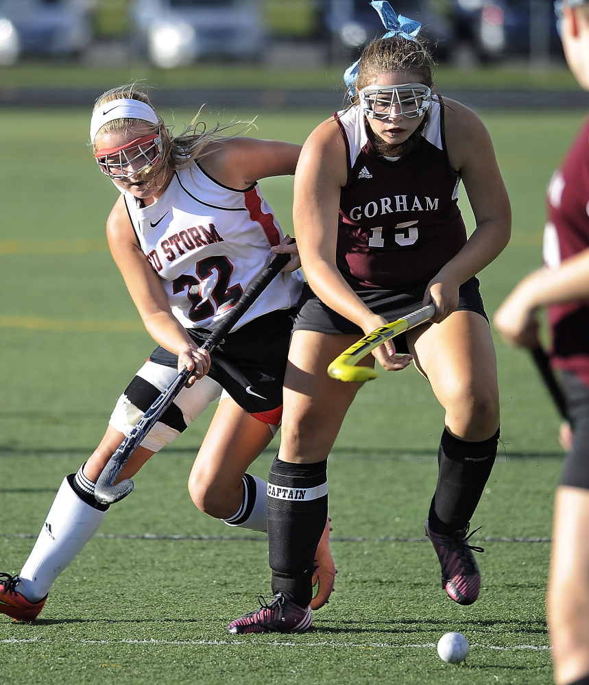 Emmy Viernes of Gorham attempts to control the field hockey ball and hold off  Kristen Levesque of Scarborough. Scarborough improved its record to 4-0 and dropped Gorham to 0-4.