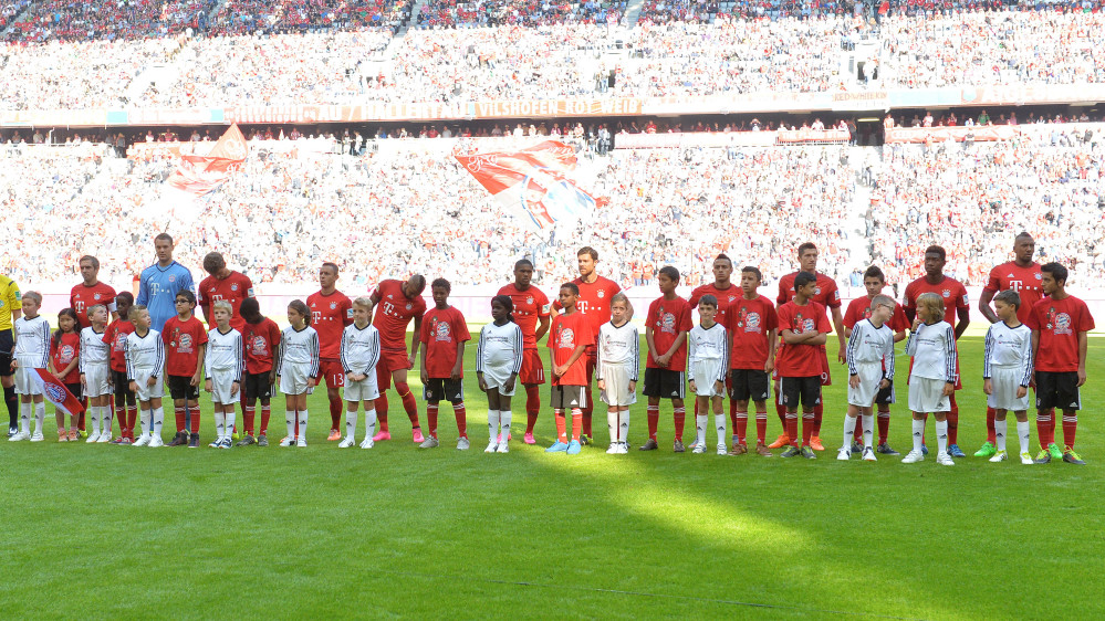 Bayern's  players stand with refugee kids on the pitch prior to the German Bundesliga soccer match between FC Bayern Munich and FC Augsburg in the Allianz Arena in Munich on Saturday.