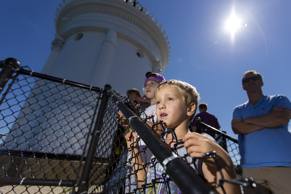 Siblings Avery, left, and Case Lappin, of South Portland, scan the waters for marine life while waiting to enter Bug Light on Saturday during Maine Open Lighthouse Day.