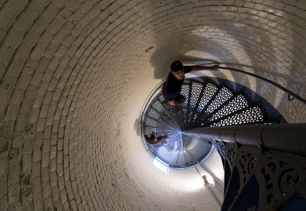 U.S. Coast Guard fireman Justin Busch leads a tour group up the spiral staircase within Portland Head Light.