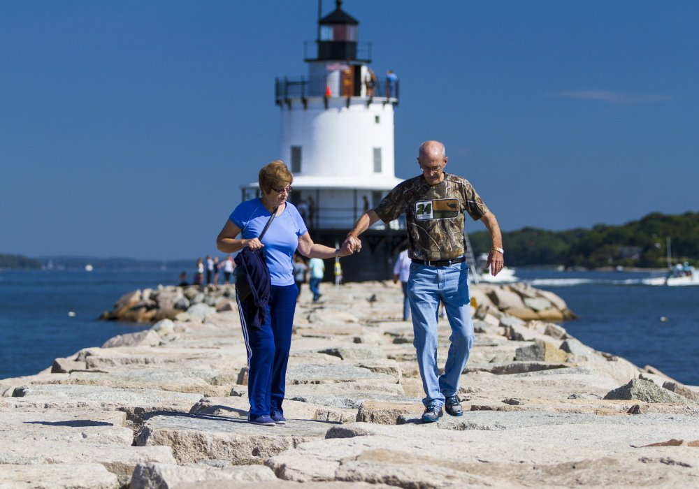 Marie and Douglas Pyle of Lewisville, Texas, stroll along the 950-foot breakwater that leads to Spring Point Ledge Lighthouse in South Portland during Maine Open Lighthouse Day on Saturday. Visitors say lighthouses are must-see icons of Maine.