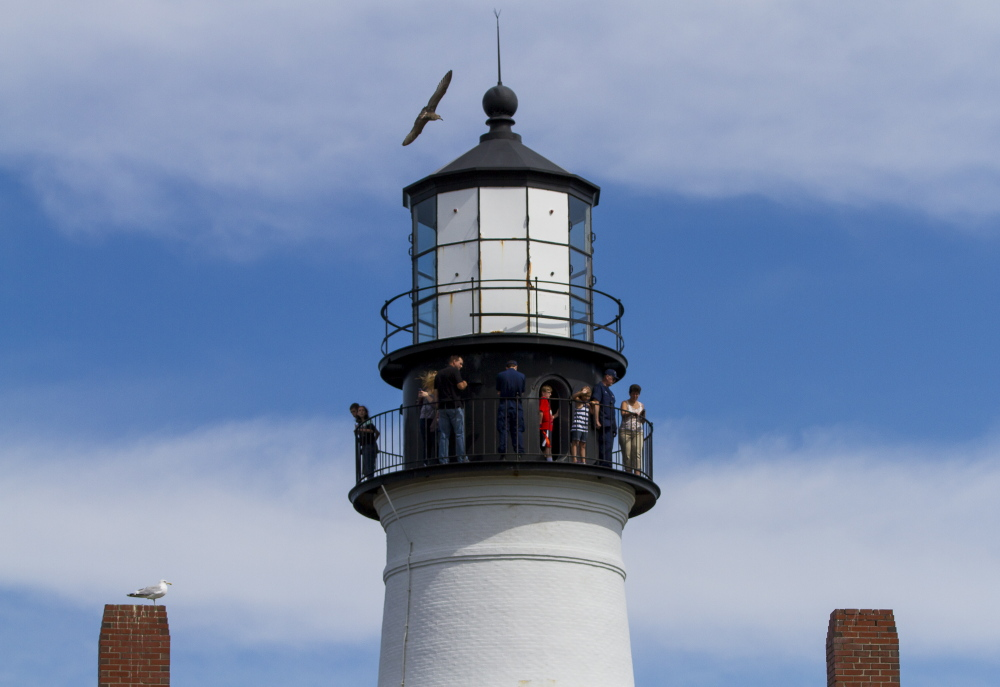Visitors take in the view from the top of Portland Head Light.