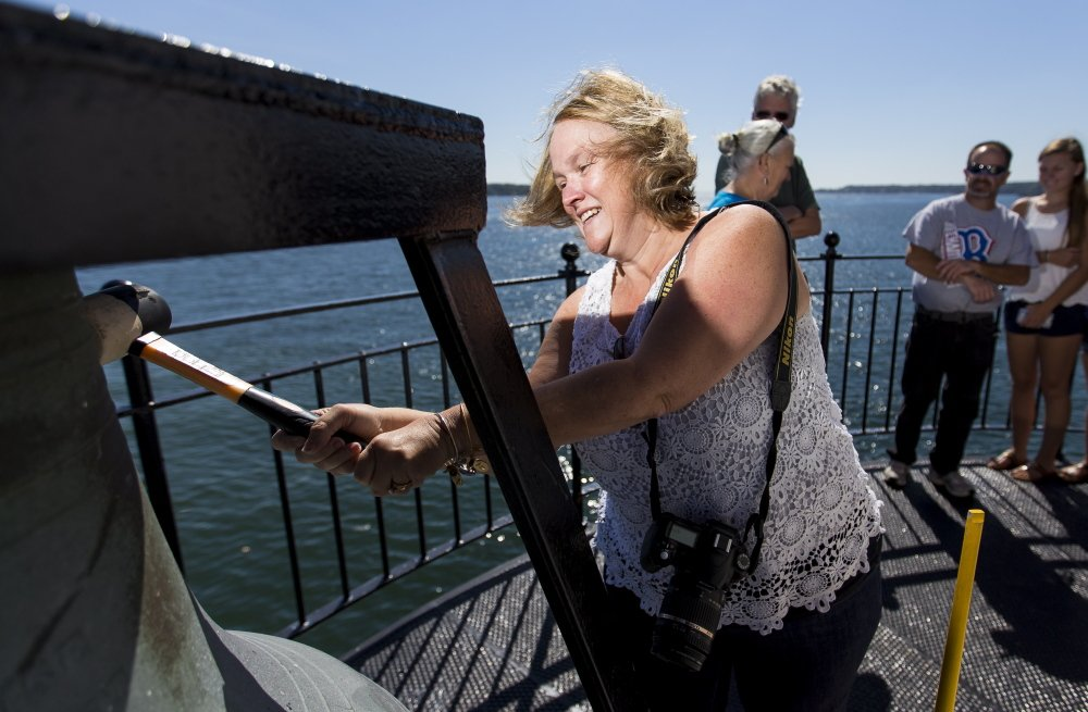 Holly Conroy, of Leominister, Mass., rings the bell at Spring Point Light during Maine Open Lighthouse Day on Saturday. Twenty-three lighthouses, including Bug Light and Portland Head Light were opened to visitors.