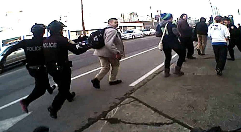 In this image from video from a Seattle police body camera video, police move in to make an arrest during a Black Lives Matter demonstration in January.