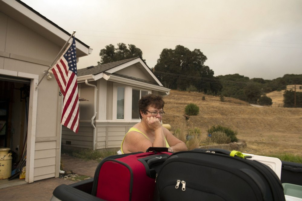 Ready to evacuate, Teri Goodall waits outside her home in San Andreas as the Butte Fire burns out of control north of San Andreas, Calif., on Friday. Jose Luis Villegas/The Sacramento Bee via AP
