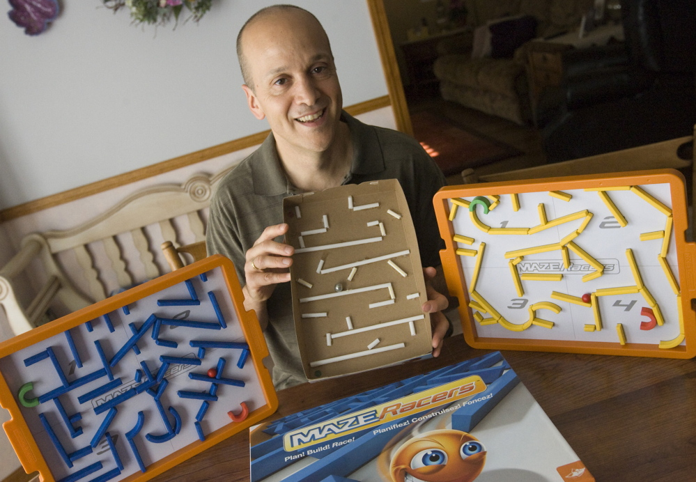 Game inventor Andy Geremia holds a prototype of his Maze Racers game, which he first constructed from a cereal box and straws at his home in Southington, Conn. After winning first place and $5,000 at a competition in 2014, he signed a licensing agreement with FoxMind Toys & Games. The game is now available on Amazon and through Barnes & Noble.
