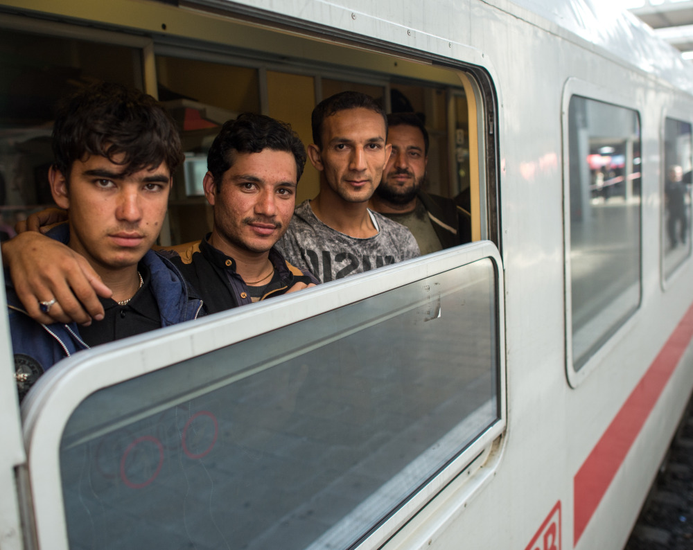 Friends Ibrahim, Hamayoun and Nomi, from left, refugees from Afghanistan, travel on a special train to Dortmund at the central train station in Munich, Germany, on Friday.