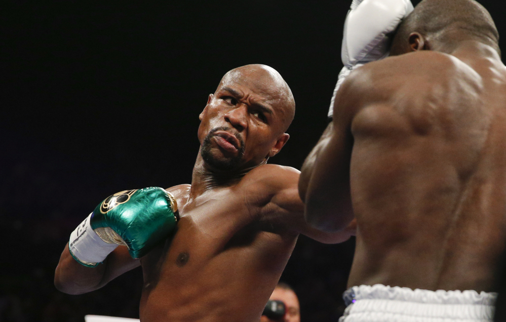Floyd Mayweather Jr. hits Andre Berto during their welterweight title boxing bout Saturday in Las Vegas.