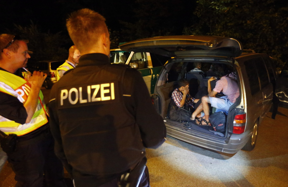 Migrants from Syria sit inside a vehicle stopped by German police on a country road heading to Freilassing, Germany, from Salzburg, Austria, on Sunday, as Germany imposed border controls to cope with thousands of migrants.