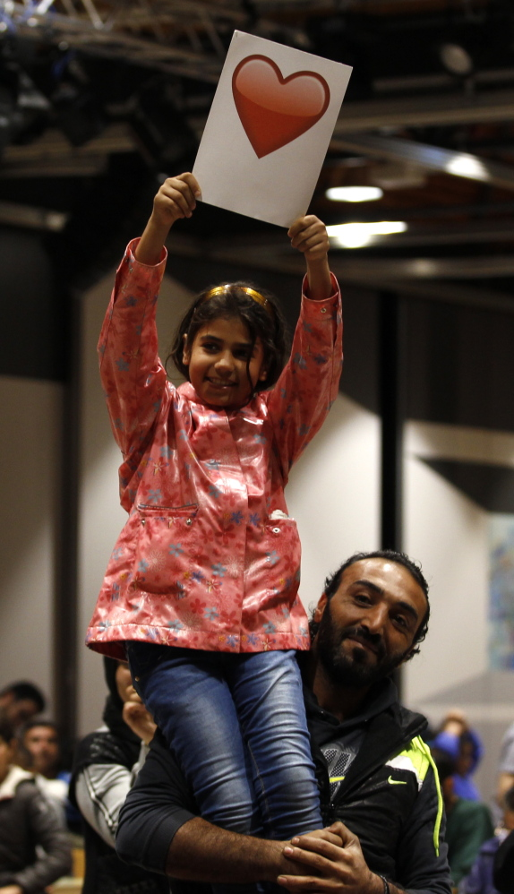 A Syrian father holds up his daughter at a reception center after their arrival at the main railway station in Dortmund, Germany, on Sunday.