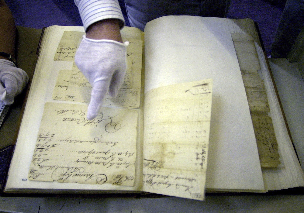 Stephen Kenney, an analyst with the Massachusetts Archives, points to one of the original writings of John Adams that are part of the collection housed in the Boston facility.