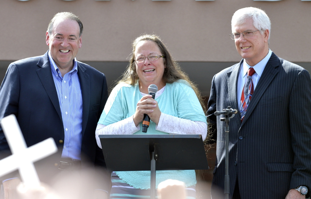 Kim Davis, with Republican presidential candidate Mike Huckabee, left, and attorney Mat Staver, founder of the Liberty Counsel, the Christian law firm representing Davis, greets the crowd after being released from jail Tuesday.